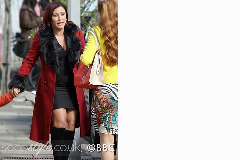 Kat wearing her red coat with black faux fur collar in EastEnders