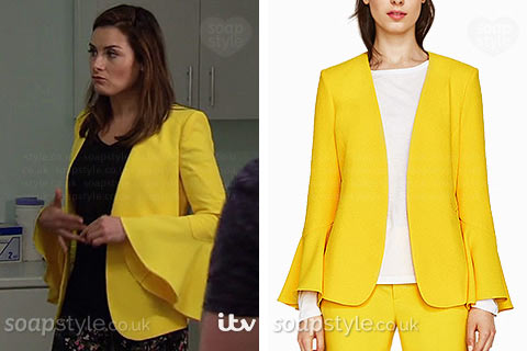 Chrissie White wearing her yellow jacket on TV in Emmerdale