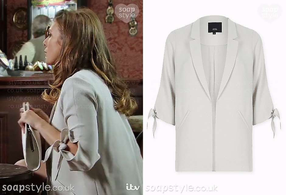 The grey blazer with tie sleeves Michelle (Kym Marsh) wears on TV in the Soap Coronation Street